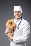 Smiling male vet with phonendoscope holding cute pomeranian dog Royalty Free Stock Images