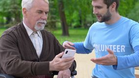 Smiling male volunteer explaining old disabled man how to use phone app, care stock video footage