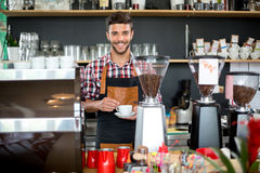 Smiling male waiter holding cup of coffee. At cafe Stock Image
