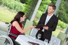 Smiling male waiter serving disabled beautiful woman. Smiling male waiter serving disabled beautiful women male Royalty Free Stock Photo