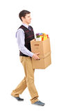 Smiling male walking with boxes Royalty Free Stock Photography