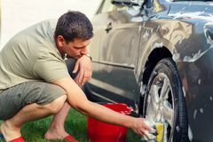 Male washing his car with a sponge and foam. Smiling male washing his car with a sponge and foam royalty free stock image