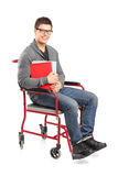 Smiling male in a wheelchair holding notebooks Royalty Free Stock Photo