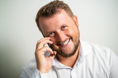 Smiling male in white shirt talking on the phone on a white gray background stock photography
