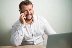 Smiling male in white shirt talking on the phone in the workplace sitting at a table near the computer stock photos