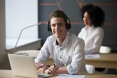 Smiling male worker in headset posing for picture. Smiling call center agent wearing headset looking at camera near laptop at workplace, happy male worker posing Stock Image