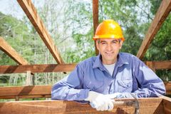 Smiling Male Worker Holding Hammer At Site Royalty Free Stock Images