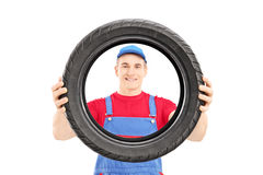 Smiling male worker holding a vehicle tire and looking at camera Stock Photos