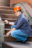 Smiling male worker measuring stone staircase with measuring tap. Young smiling male worker measuring stone staircase with measuring tape Stock Photos