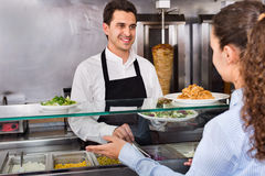 Smiling male worker serving customer with smile at shawarma plac. Friendly smiling male worker serving customer with smile at shawarma place Stock Photos