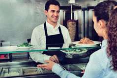 Smiling male worker serving customer with smile at shawarma plac. Friendly smiling male worker serving customer with smile at shawarma place Royalty Free Stock Photo
