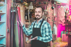 Smiling male worker showing new belts in leather workshop Royalty Free Stock Images