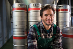 Smiling male worker sitting by kegs at warehouse royalty free stock photos