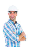 Smiling male worker standing arms crossed. Smiling male worker wearing hardhat while standing arms crossed on white background Royalty Free Stock Image