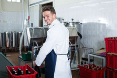 Smiling male worker using machine at sparkling wine factory. Smiling male worker using machine to bottle wine at sparkling wine factory Royalty Free Stock Photography