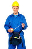 Smiling male worker wearing yellow safety hat. Holding measuring tape Royalty Free Stock Images