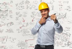 Smiling male worker in yellow hard cap holding a pen. Royalty Free Stock Photo