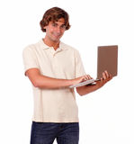 Smiling male working on a laptop. Portrait of a young handsome hispanic male in jeans using his laptop on white background Stock Image