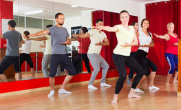 Smiling males and females dancing. Adult males and females smiling and dancing contemp dance in studio Stock Photos