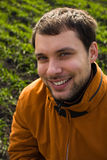 Smiling man. In orange jacket on blurry green grass Royalty Free Stock Photography