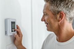 Smiling Man Adjusting Thermostat On Home Heating System. A Smiling Man Adjusting Thermostat On Home Heating System stock photo