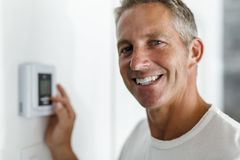 Smiling Man Adjusting Thermostat On Home Heating System. A Smiling Man Adjusting Thermostat On Home Heating System stock image