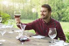 Smiling man admires red wine Royalty Free Stock Photography