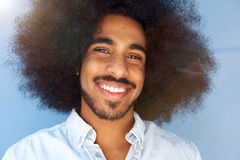 Smiling man with afro and beard by blue wall royalty free stock photo