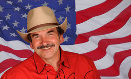 Smiling man against US flag. A portrait of a man smiling. Model resembles Burt Reynolds.  US flag background Royalty Free Stock Photography