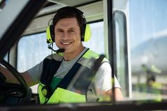 Smiling man from airport service personnel sitting behind the wheel royalty free stock image