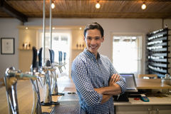 Smiling man with arms crossed at counter in restaurant. Portrait of smiling man with arms crossed at counter in restaurant Stock Photos
