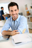 Smiling man with arms crossed sitting in office Royalty Free Stock Images