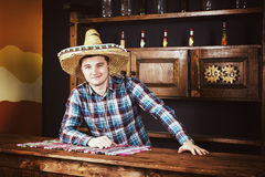 Smiling man as bartender in a sombrero leaned on bar counter in. Mexican pub, a shelf with spicy sauces and empty bottles in the background stock images