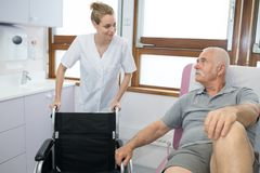 Smiling man asking doctor about wheelchairs stock photography