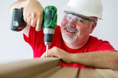 Smiling man assembling wood with drill-drive stock photography