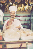 Smiling man assistant showing piece of meat. In butcher's shop Royalty Free Stock Photo