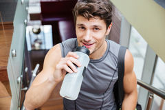 Smiling man athlete walking and drinking water in gym. Smiling handsome young man athlete walking and drinking water after training in gym royalty free stock photography