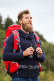 Smiling man with backpack and binocular outdoors Stock Images