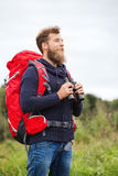Smiling man with backpack and binocular outdoors Royalty Free Stock Photos