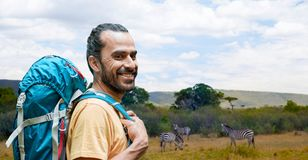Smiling man with backpack over african savannah Royalty Free Stock Image