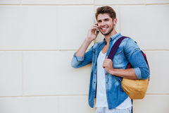Smiling man with backpack standing and talking on mobile phone Royalty Free Stock Photo