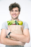 Smiling man with bag full of groceries. Looking at camera Royalty Free Stock Image
