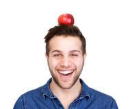 Smiling man balancing apple on head. Close up portrait of a smiling man balancing apple on head isolated white background Stock Image