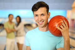 Smiling man with ball; couple stands behind him Stock Photo