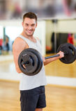 Smiling man with barbell in gym Stock Photography