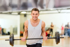 Smiling man with barbell in gym Stock Image