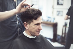 Smiling man in barbershop watching the process of hair cutting Stock Photos