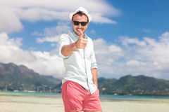 Smiling man on the beach making the ok sign Royalty Free Stock Images