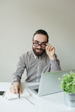 Smiling man with beard in glasses taking notes with laptop notep Royalty Free Stock Photo