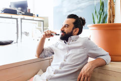 Smiling man with beard and hair bun at office Stock Photography